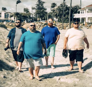 Four guys walking barefooted