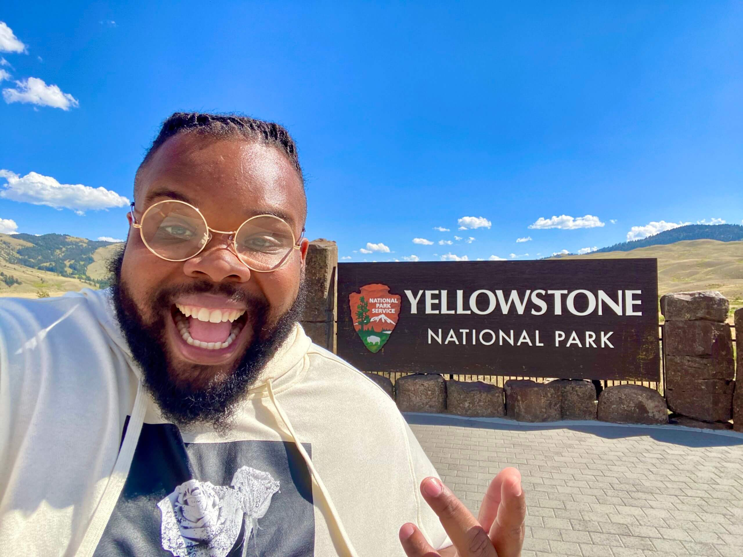 Jeff Jenkins smiling in front of Yellowstone National Park Sign