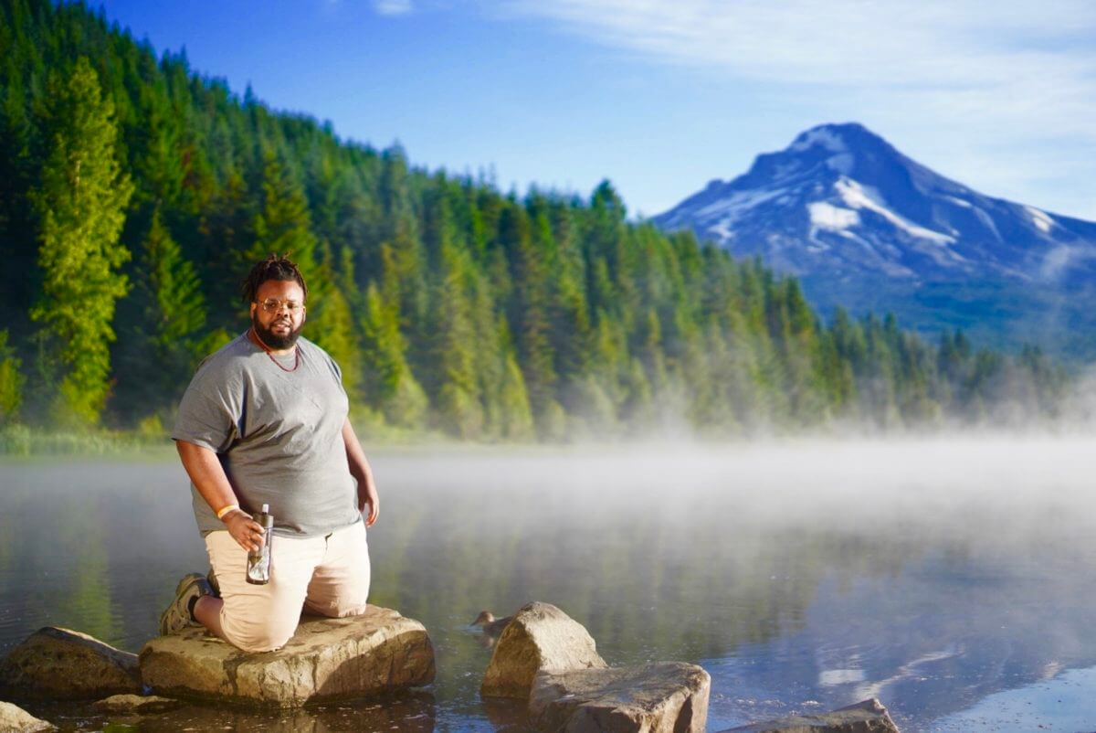 Jeff Jenkins on knees in front of lake in Government Camp, Oregon with Mount Hood behind him