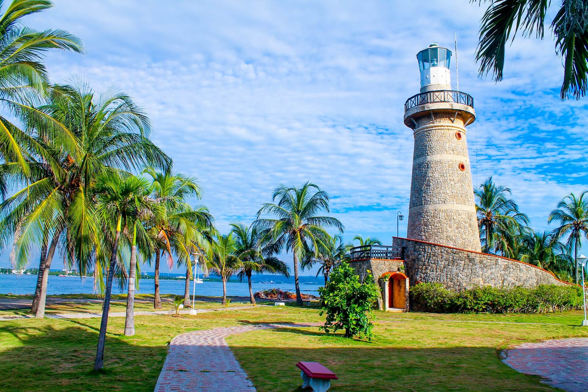 Photo of lighthouse in Cartegena made of stnes with a white top. Palm trees to the left, green grass, white clouds cover most of the blue sky.